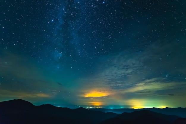 La corriente de nubes sobre montañas con estrellas. tarde noche