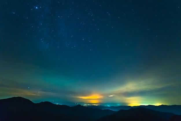 La corriente de nubes sobre montañas con estrellas.