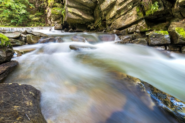 Corriente de río que fluye rápidamente con agua suave que cae de grandes piedras