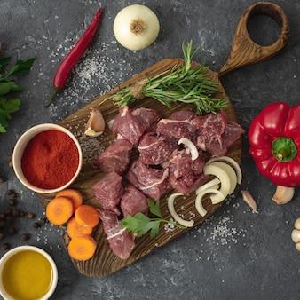 Corta la carne con vegetales. mesa de cocina con ingredientes para cocinar carne y verduras