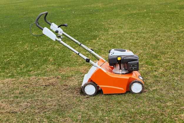 Cortacésped naranja de pie en el suelo sobre la hierba verde