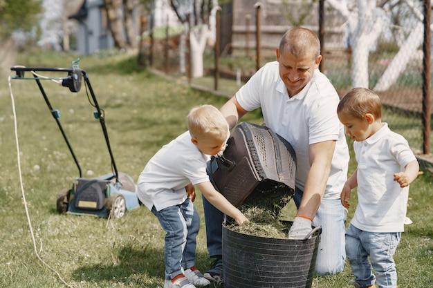Cortadora de césped hombre trabajando en el patio trasero con hijos