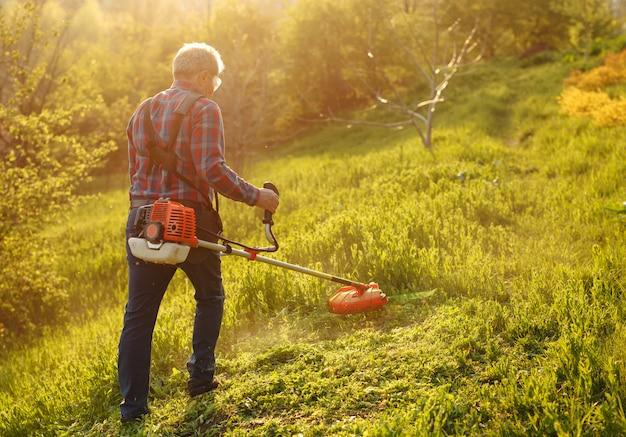 Cortadora de siega - hierba del corte del trabajador en yarda verde en la puesta del sol.