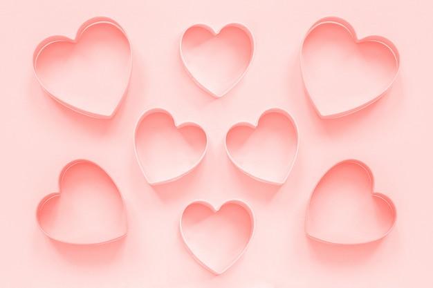 Cortadores de color rosa galletas en forma de corazón en tono colar. amor romantico patron, plantilla