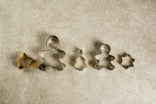 Cortadores de galletas de navidad en la mesa de piedra de cocina gris - árbol de navidad, hombre de jengibre, estrellas. vista superior copia espacio, concepto de horneado de navidad