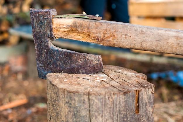 Cortando madera con hacha. hacha atorada en un tronco de madera
