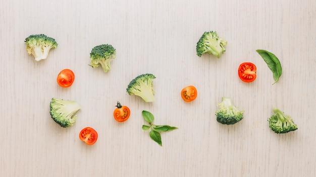 Cortar el brócoli; albahaca y tomates cherry a la mitad en tablón de madera