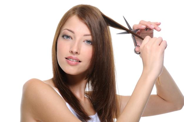 Cortar el cabello de la joven hermosa morena con unas tijeras