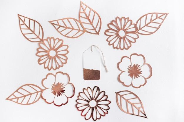 Cortar flores y hojas de oro con etiqueta en el centro sobre fondo blanco
