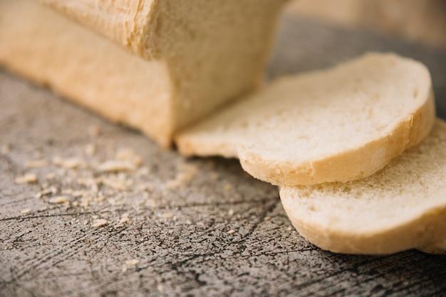Cortar hogaza de pan blanco sobre mesa gris