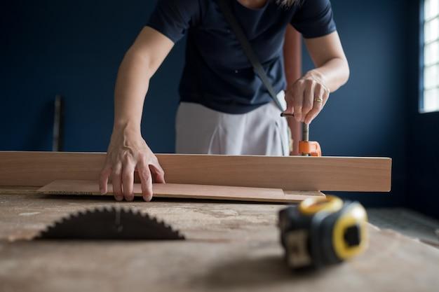 Cortar madera para la construcción, taladro de madera, carpintero, trabajador