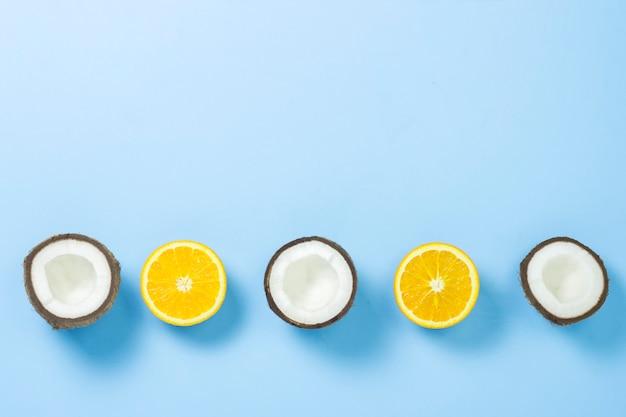 Cortar la naranja y el coco sobre una superficie azul. vista plana, vista superior.