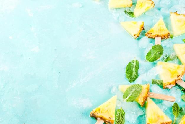 Cortar palitos de paleta de piña y hojas de menta sobre fondo azul claro con hielo concepto de verano