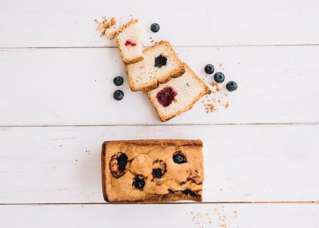 Cortar pastel con mermelada y arándanos en mesa de madera