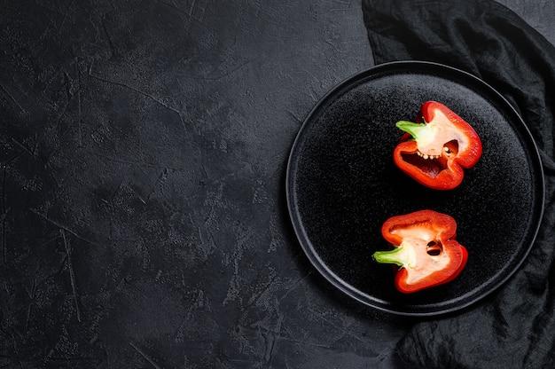 Cortar el pimiento rojo, dos mitades. fondo negro. vista superior. espacio para texto