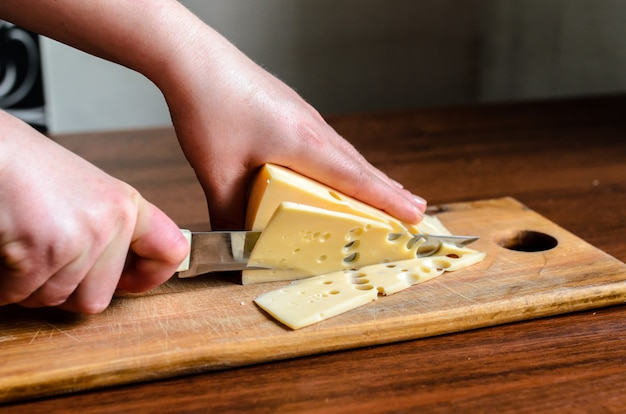 Cortar el queso en una tabla de madera.
