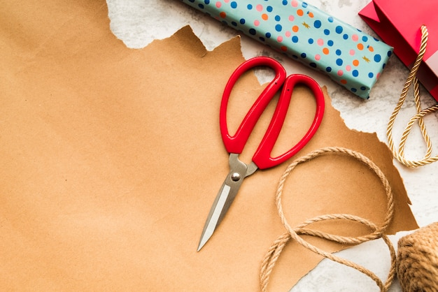 Cortar con tijeras; cuerda de yute y caja de regalo envuelta sobre papel marrón.