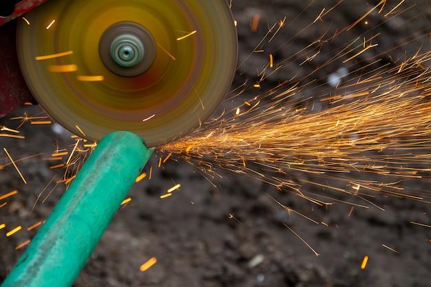 Cortar un tubo de metal con una sierra circular con salpicaduras de chispas.