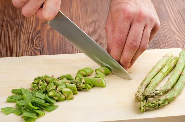 Cortar las verduras con un cuchillo de cocina en el tablero
