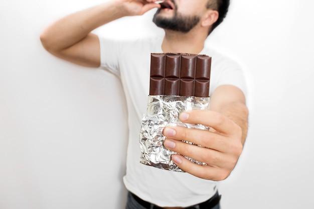 Corte la barra de chocolate en la mano del joven. el lo sostiene. también el chico pone un pedazo de chocolate en la boca con otra mano. es delicioso.