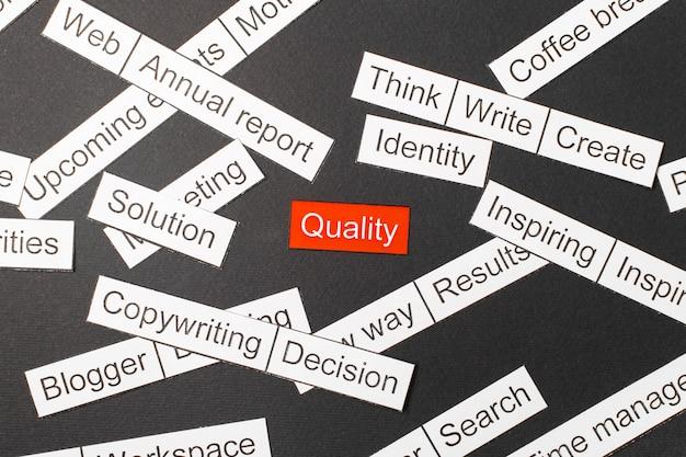 Corte la calidad de la inscripción en papel en rojo, rodeada de otras inscripciones en un fondo oscuro. nube de palabras.
