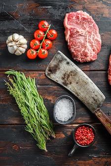 Corte de carne orgánica de la hoja superior, filete de ternera cruda marmolada, con una vieja cuchilla de carnicero y condimentos en una mesa rústica de madera oscura, vista superior con espacio para texto.