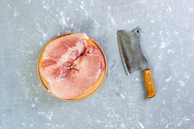 Corte crudo del hombro de cerdo a bordo con cuchillo o hacha de cocina. cuchilla con carne cruda fresca sobre fondo de hormigón gris