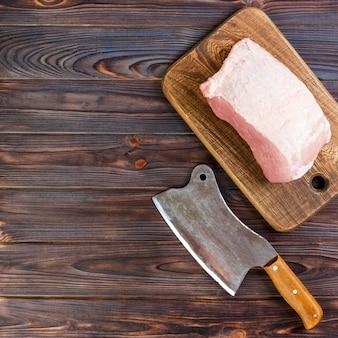 Corte crudo del hombro de cerdo a bordo con cuchillo o hacha de cocina.