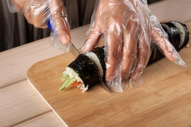 Corte el kimbap (plato coreano de arroz enrollado) con un cuchillo azul. mano de mujer con guante de plástico, haciendo gimbap, corte de kimbap, rollo coreano de gimbap (kimbob o kimbap). paso a paso haciendo kimbop