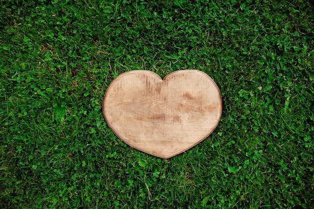 Corte de madera en forma de corazón en el fondo de la hierba verde