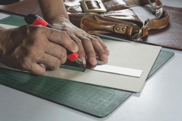 Corte de mano masculino con un cuchillo al patrón para el bolso. concepto de producto hecho en casa.