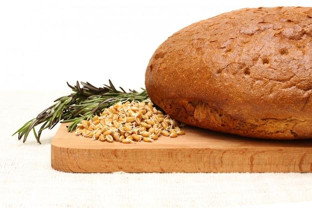 Corte el pan, el trigo germinado, la hierba y la tabla de madera sobre manteles de lino blanco.