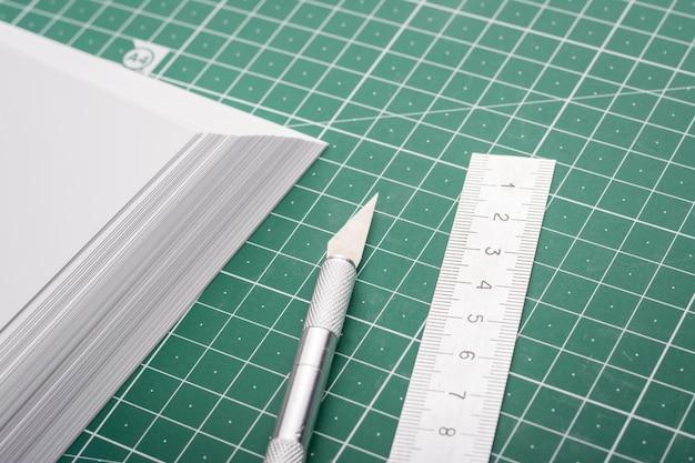 Corte de papel fotográfico con bisturí y regla sobre estera de corte