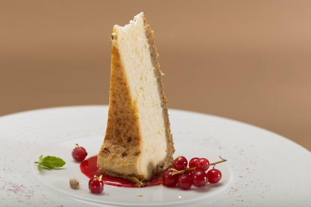 Corte el pastel de queso con frutas del bosque y grosellas rojas, menta y pan de oro en un plato blanco