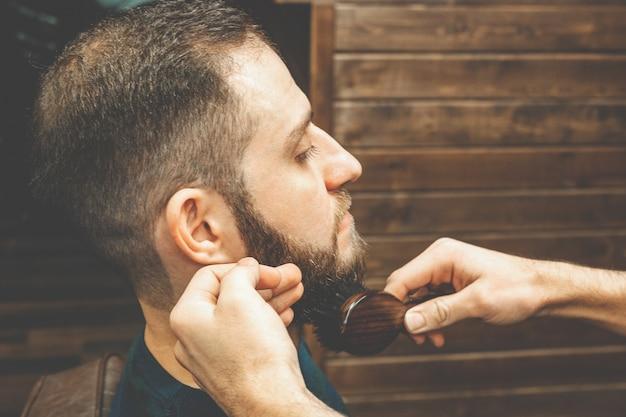 Corte de pelo cabeza y barba en una barbería. barber se pone y se peina la barba del cliente. proceso de crear un peinado y peinar una barba para hombres. hombre en una barbería. estilista de equipos. enfoque selectivo