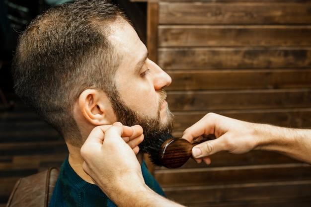 Corte de pelo cabeza y barba en una barbería. barber se pone y peina la barba del cliente. proceso de crear un peinado y peinar una barba para hombres. hombre en una barbería. estilista de equipos. enfoque selectivo
