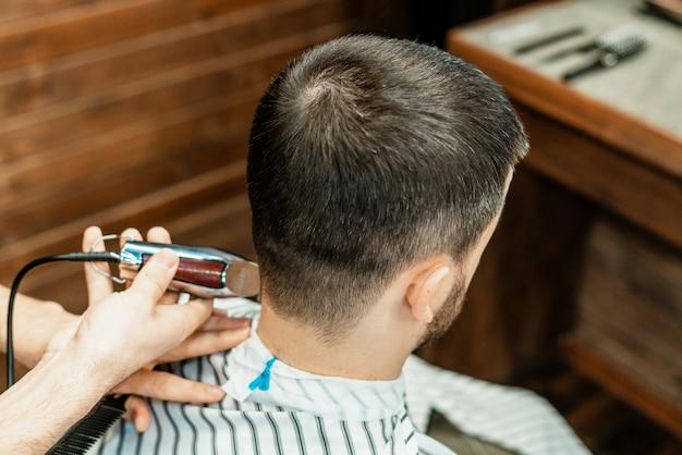 Corte de pelo en la peluquería. peluquero corta el pelo en la cabeza del cliente