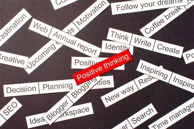 Corte el pensamiento positivo de inscripción en papel sobre un fondo rojo, rodeado de otras inscripciones sobre un fondo oscuro. concepto de nube de palabras.
