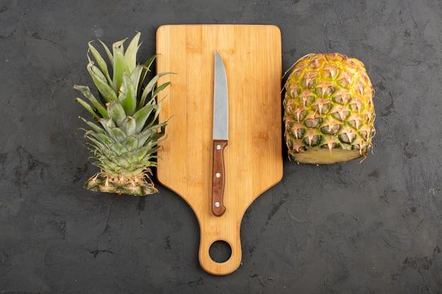 Corte la piña jugosa madura fresca junto con un escritorio de madera y un cuchillo de tamaño mediano sobre un fondo gris