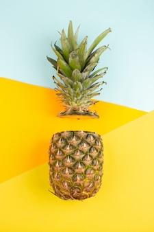 Corte la piña suave y jugosa en el escritorio azul hielo y amarillo