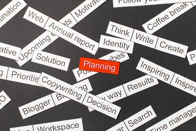 Corte la planificación de inscripción en papel sobre un fondo rojo, rodeada de otras inscripciones sobre un fondo oscuro. nube de palabras.