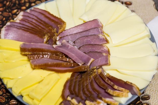 Corte de quesos y productos cárnicos. en un plato gris