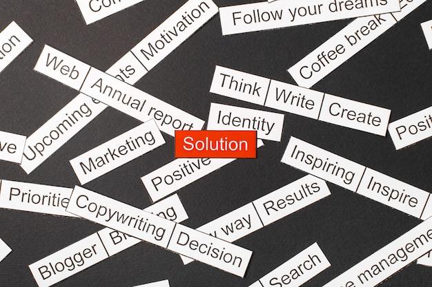 Corte la solución de inscripción en papel sobre un fondo rojo, rodeada de otras inscripciones sobre un fondo oscuro. concepto de nube de palabras.