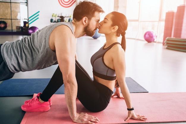 Corte la vista de un chico parado en una posición de tabla alta mientras su novia lo besa.