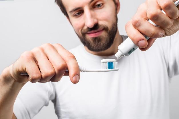 Corte la vista de un hombre que pone pasta de dientes en un cepillo de dientes. quiere limpiarse los dientes. guy se ve feliz y satisfecho. de cerca. aislado en la pared blanca