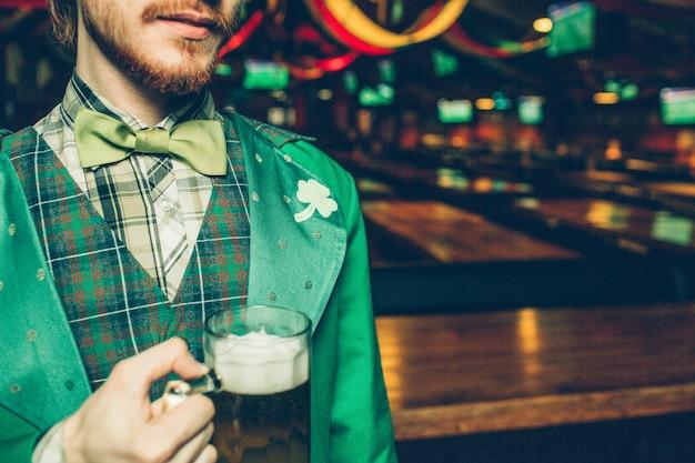 Corte la vista del hombre en traje verde de san patricio en el pub y sostenga la jarra de cerveza. guy está solo en la habitación.