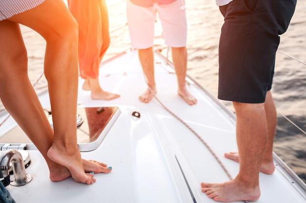 Corte la vista de las piernas de la gente. dos hombres y dos mujeres se paran uno frente al otro. pasan tiempo juntos.