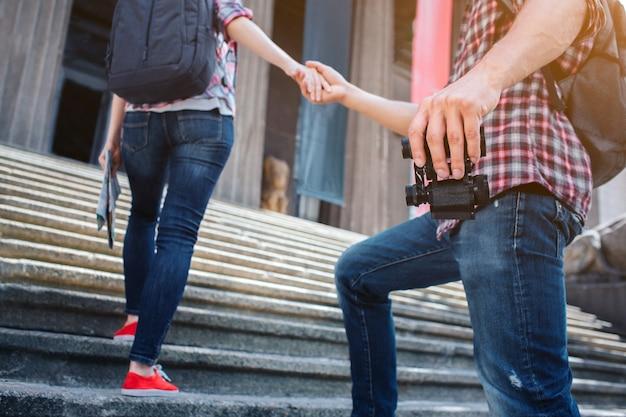Corte la vista de los turistas subiendo escalones. sostiene binoculares y usa saco de roca. ella sostiene su mano. la mujer también usa rocksack. la mujer tiene un mapa en la mano.