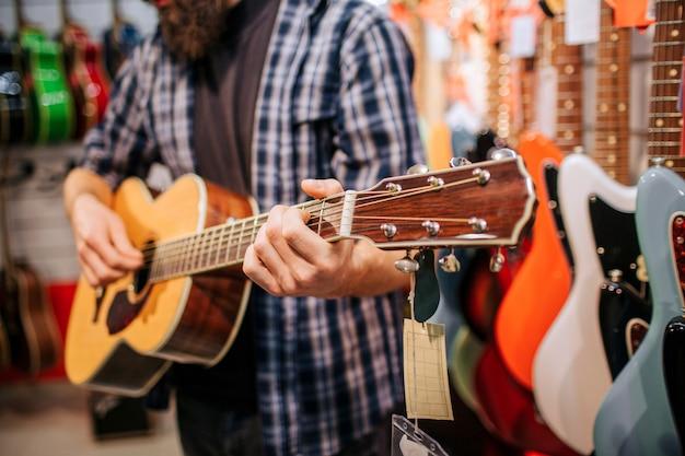 Corte vuew del hombre de pie y tocando la guitarra acústica. se para en la tienda de música. muchas guitarras electrónicas están detrás.