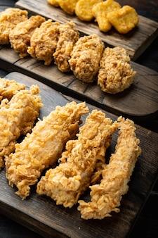 Cortes de pollo frito del sur sobre la mesa de madera oscura.